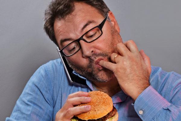 On phone while eating burger.fat man eating hamburger.